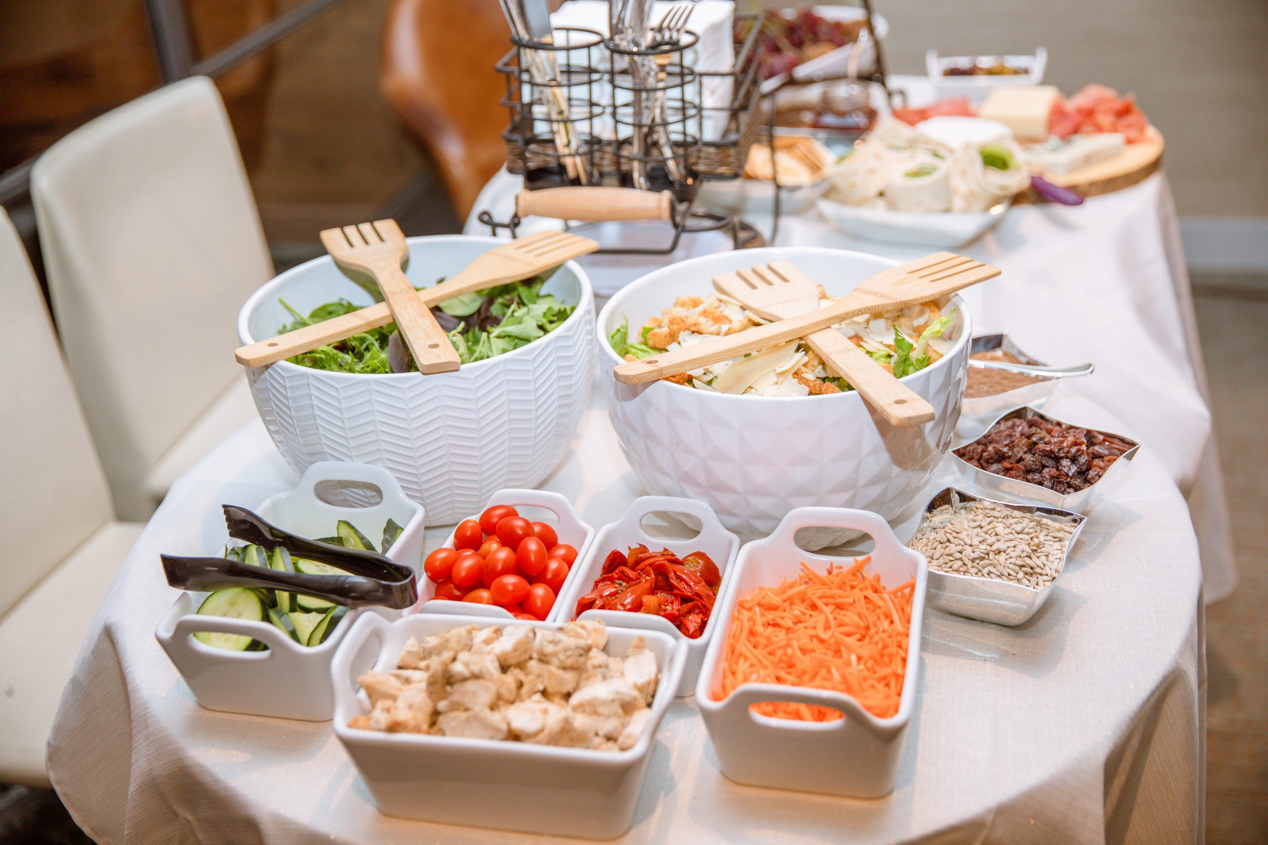 two white tables covered in white tablecloths with a salad bar sitting on top with lettuce, carrots, cucumbers, tomatoes, chicken, cheese and utensils