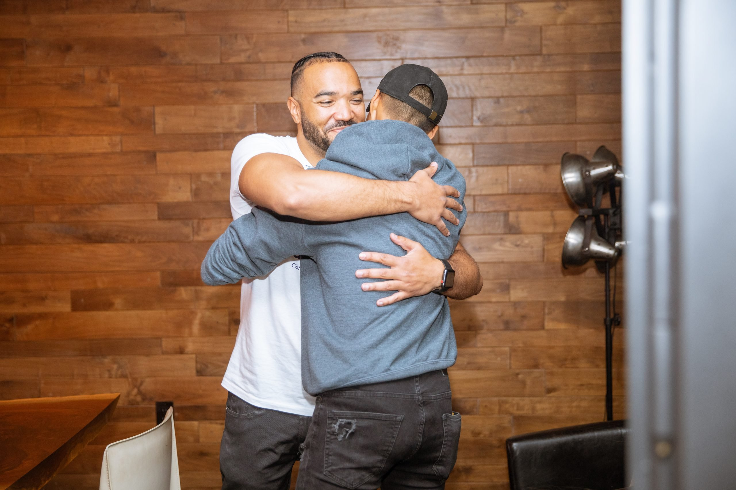 A man wearing a white shirt hugs another man wearing a blue sweatshirt in front of a wooden wall