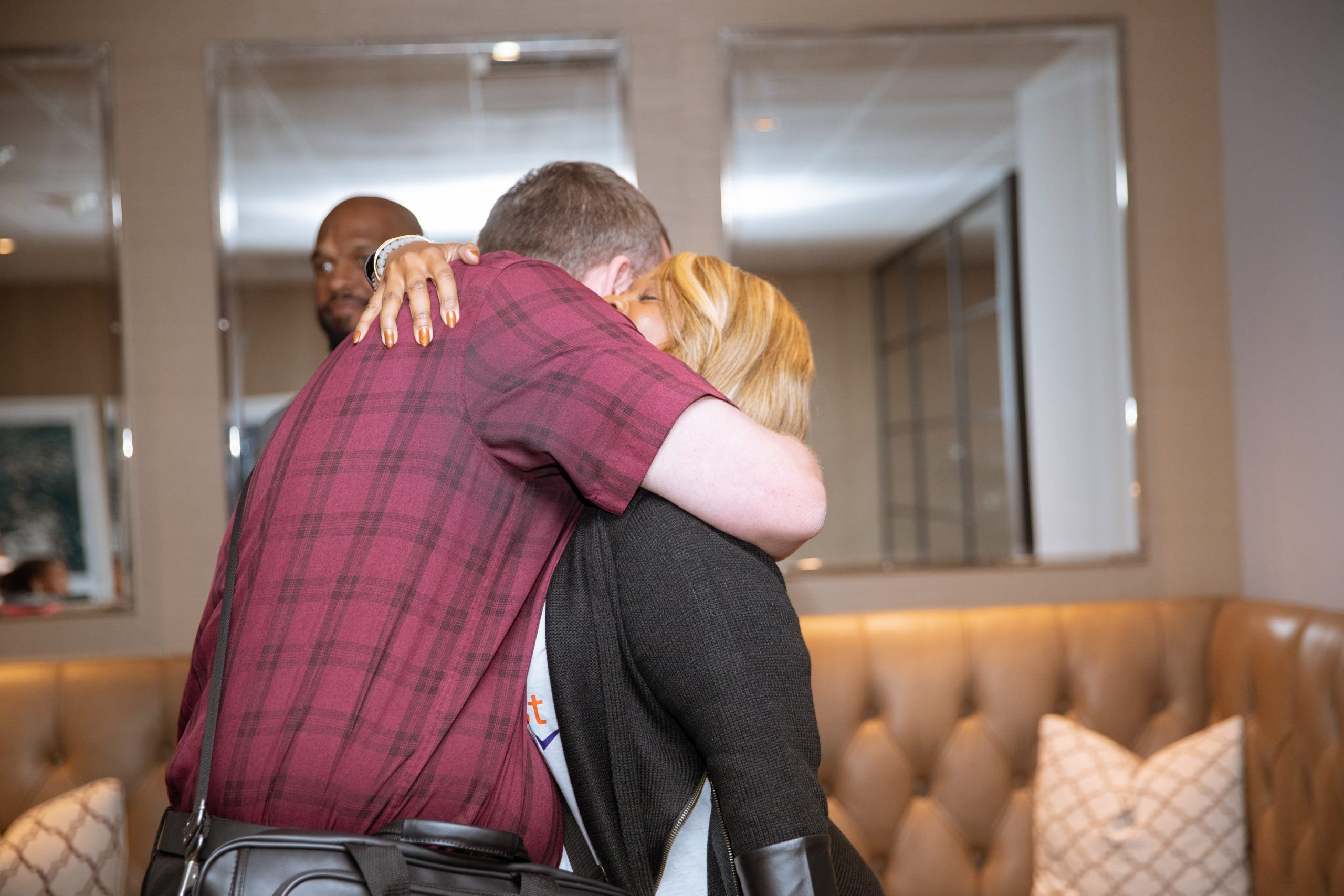 Founder Lisa Bailey wears a black cardigan and hugs a man wearing a red plaid shirt with a crossbody briefcase