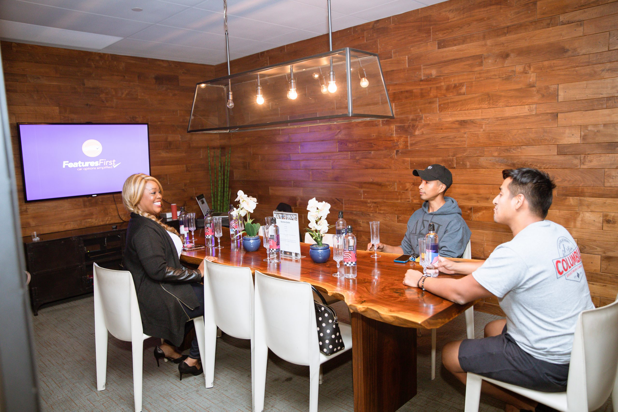 Founder Lisa Bailey sits at a wooden table talking with two men with a TV on the wall displaying the FeaturesFirst logo on a purple background