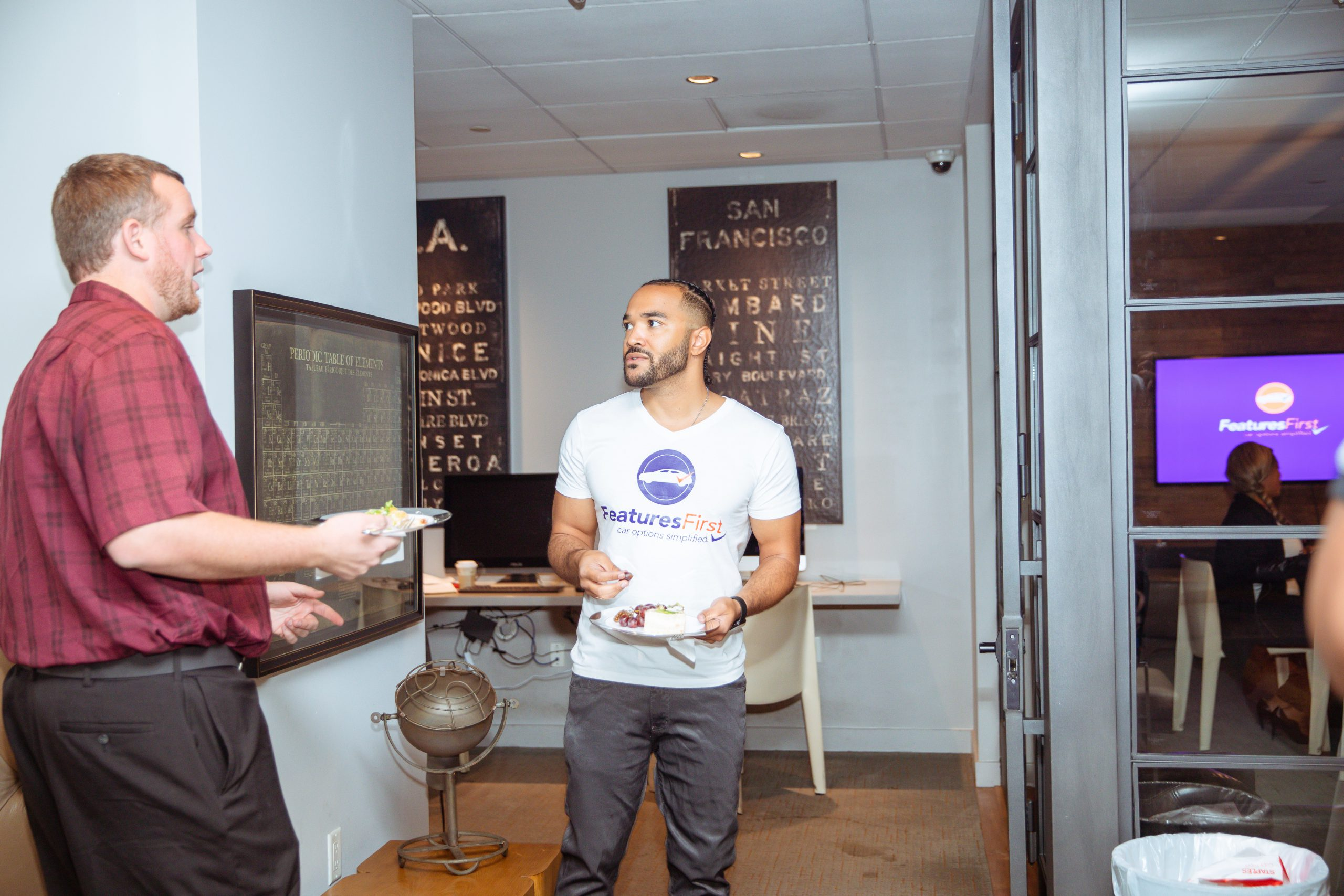 A man wears a FeaturesFirst shirt talking to a man in a red plaid shirt, both standing in a hallway and holding plates of food