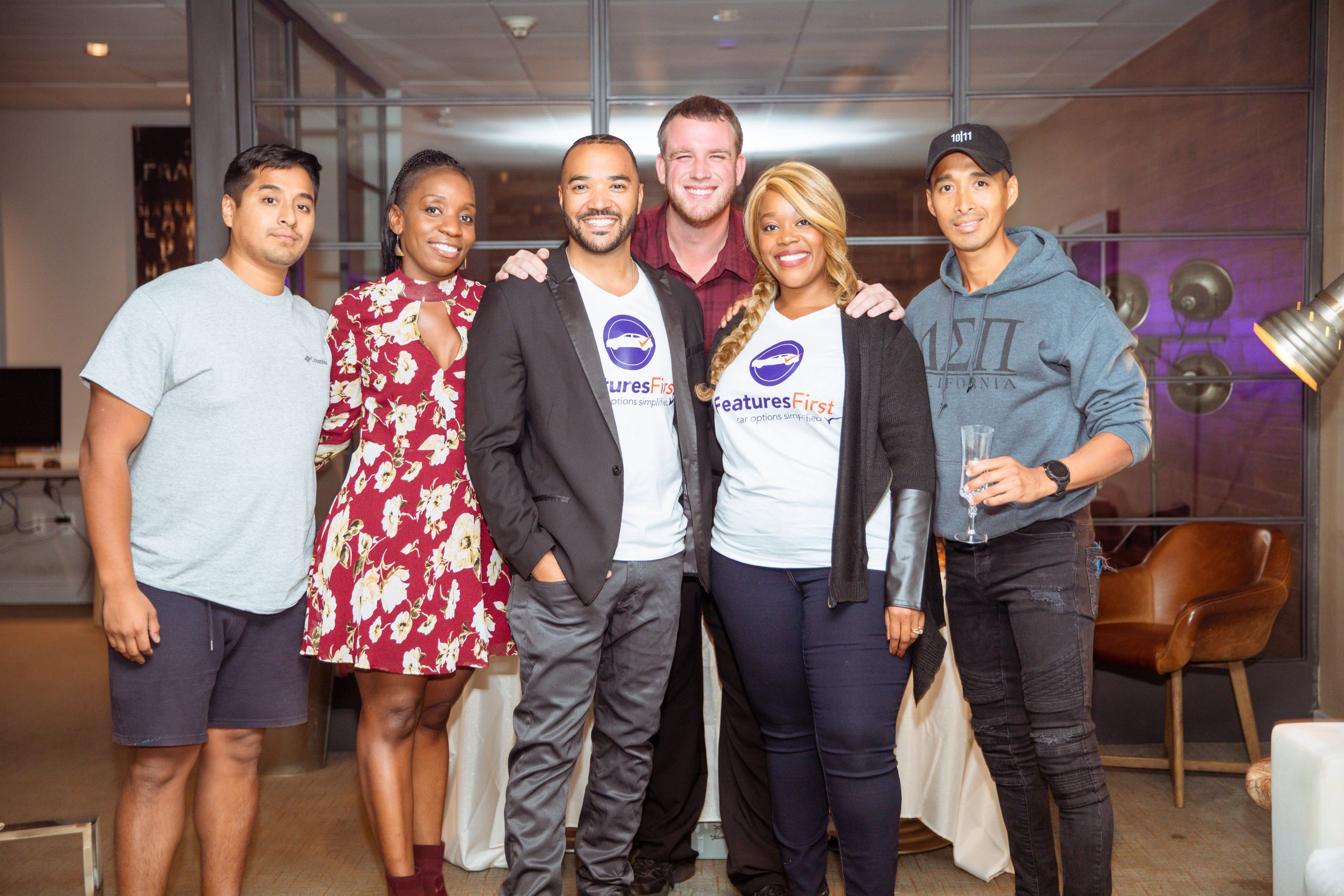 Founder Lisa Bailey and a man wearing FeaturesFirst shirts and stand for a photo with four other people in front of a glass wall
