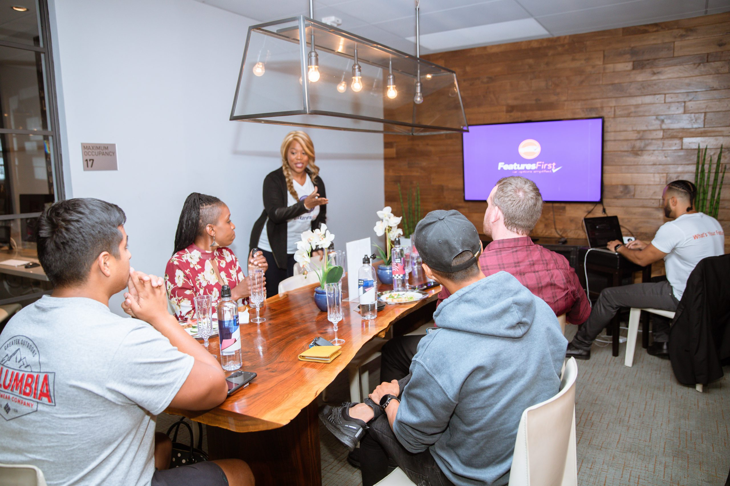 Founder Lisa Bailey stands next to a wooden table with five people sitting as they look at powerpoint presentation on the wall with the FeaturesFirst logo on a purple background